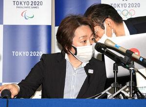 記者会見中にスタッフから耳打ちをされる東京五輪・パラリンピック組織委の橋本聖子会長(左)(代表撮影)