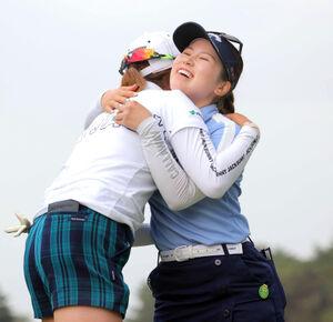 通算14アンダーで優勝を飾り、大里桃子(左)と抱き合う西村優菜