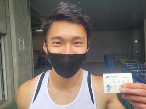 男子400メートルを制し、自身の名刺を手に笑顔の山木伝説(かける)