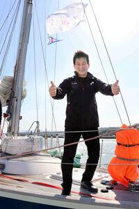 大阪・岬町の淡輪ヨットハーバーから出港前、ヨット上でサムアップポーズを見せる辛坊治郎氏