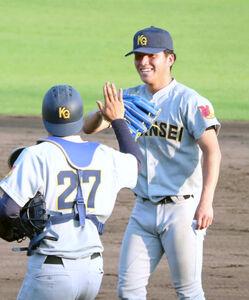 2試合連続完封した関学大の黒原拓未(右)は捕手の佐藤海とハイタッチ