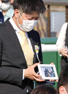 岡田総帥の遺影を手に、表彰式を見守る関係者