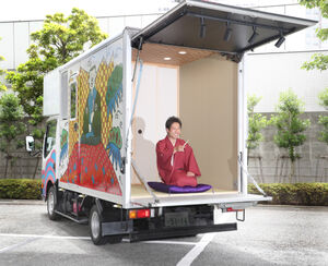 トラック荷台を改造した「落語カー」で来社した落語家の橘家文太
