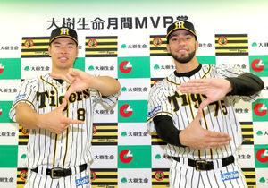 月間MVP賞を受賞しポーズをとる佐藤輝(左)とスアレス