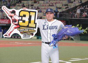 開幕31試合連続無失点の日本タイ記録を達成し記念ボードを掲げる平良海馬