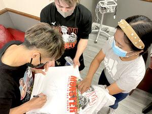 ボクシング・ファンの看護士(右)にサインをする井上尚弥(左、中央は太田トレーナー、大橋ジム提供)