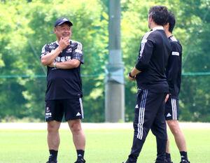 コーチ陣と話す松永英機監督(左)