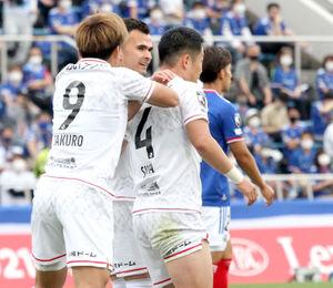 前半7分、オウンゴールを誘発するクロスを上げた札幌MF菅大輝(右)は、仲間に祝福される