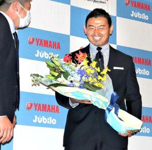 引退会見で花束を受け取り笑顔の五郎丸歩