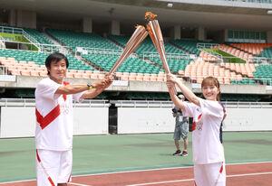エコパスタジアムで中山コーチ(左)から聖火を受けた歌手の百田夏菜子(代表撮影)
