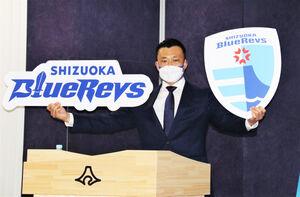 新チームのロゴとエンブレムを掲げる山谷社長
