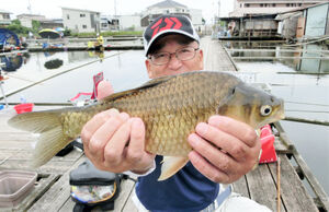 一緒に釣りをした妹山さんは36.7センチのヘラブナを仕留めてニッコリ