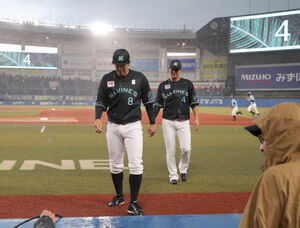 豪雨の仲、ベンチに戻る中村奨吾(手前)と藤岡裕大(右)