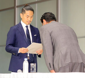 井岡一翔(左)に謝罪文を手渡し頭を下げるJBCの永田有平・理事長