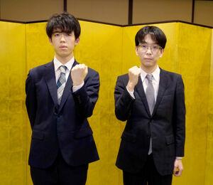 気合のガッツポーズを見せる藤井聡太王位(左)と豊島将之竜王(日本将棋連盟提供)