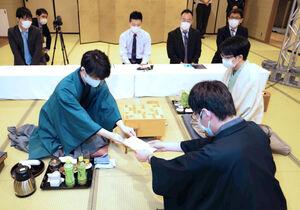 封じ手を立会人に手渡す藤井聡太王位(左)と豊島将之竜王