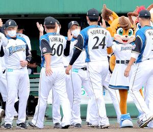 野村佑希(中央右)らナインを出迎える栗山英樹監督(中央)
