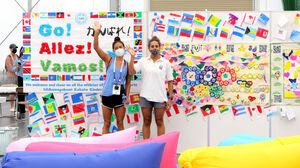 事前キャンプで、地元の子どもたちが作製した応援ボードのあるリラクゼーションルームでカメラに気づき、手を振る選手たち(カメラ・竜田 卓)