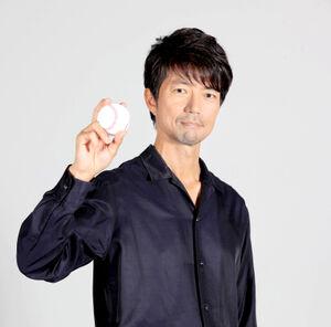 野球ボールを手にポーズをとる仲村トオル(カメラ・堺 恒志)