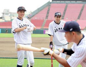 バント練習をする村上宗隆(手前)を山田哲人(後方右)と談笑しながら見つめる坂本勇人