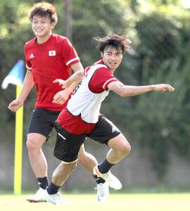 笑顔でボールを追いかける三笘薫(左は上田綺世)