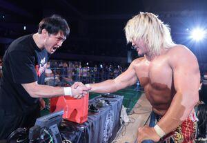 KENTAに快勝後、アシストを受けた放送席の柴田勝頼(左)と握手する棚橋弘至(新日本プロレス提供)