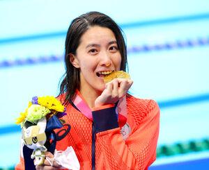 表彰式で金メダルをかむポーズを見せる大橋悠依