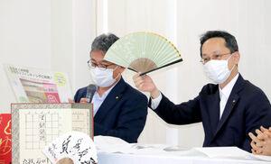 藤井聡太二冠の「3一銀」扇子を広げる井上慶太常務理事(右)