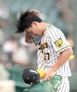 2回に6点を失い頭を押さえながらベンチに戻る阪神先発・伊藤将司