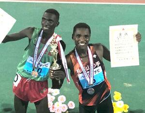 男子5000メートル表彰式で笑顔をみせるキンヤンジュイ(左は優勝したムワンギ)