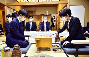 盤駒の感触を確かめる豊島将之叡王(右)と藤井聡太二冠(日本将棋連盟提供)