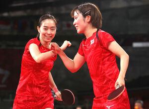 笑顔でタッチする石川佳純{左)と平野美宇(ロイター)
