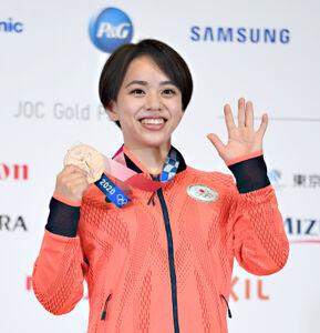 村上茉愛は、メダルを手に笑顔で撮影に応じた(代表撮影)