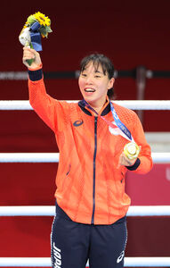 女子フェザー級決勝で勝利し、金メダルを手に笑顔を見せる入江聖奈(カメラ・相川 和寛)