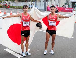 銀メダルの池田(左)と銅メダルの山西が日の丸を背にポーズをとった