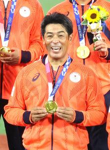 菊池涼介に金メダルをかけてもらいうれしそうな稲葉篤紀監督(カメラ・竜田 卓)