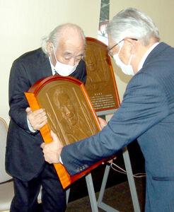 野球殿堂博物館から、レリーフのレプリカを贈られる佐山和夫氏(左)