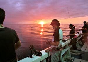 夕日に照らされた船内はイカ釣りを楽しむファンでにぎわった