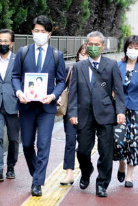 妻・真菜さんと長女・莉子ちゃんの遺影を手に東京地裁に向かう松永拓也さん(左)と真菜さんの父・上原義教さん