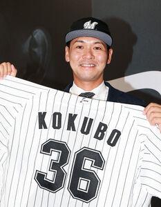 ロッテに入団した元広島・小窪哲也は、背番号36のユニホームを手に笑顔(代表撮影)