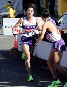 第97回箱根駅伝、駒大3区の小林歩(右)にタスキを渡す2区の田沢廉