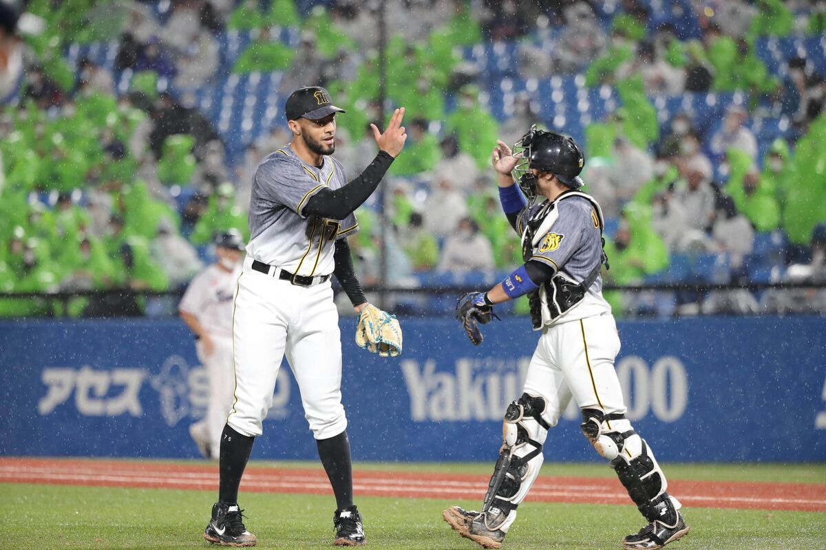 最後を締め、梅野隆太郎(右)とタッチを交わすロベルト・スアレス(カメラ・岩崎 龍一)
