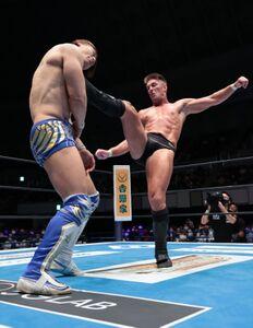 飯伏幸太(左)に強烈なキックを浴びせるザック・セイバーJr.(新日本プロレス提供)